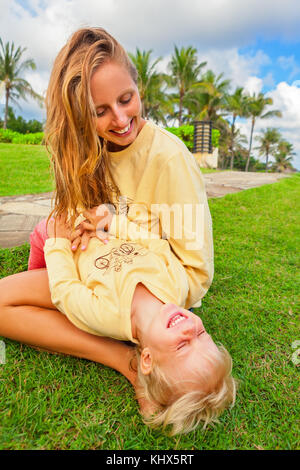 Happy family on green grass lawn. Child have fun on outside walk - mother tickling funny baby son lying on her laps. Active people activity on tropica