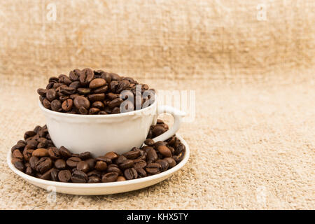 Coffee cup filled with roasted beans on jute text area or copy space - Stock Photo