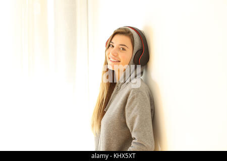 Portrait of a teen posing looking at you listening to music wearing headphones isolated on white at side