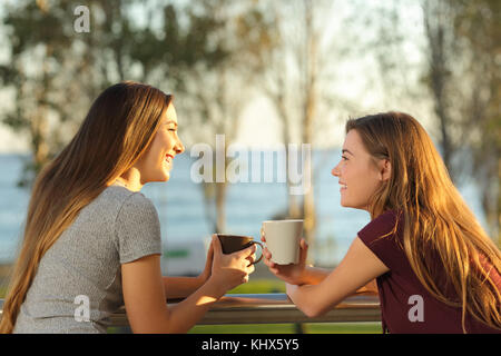 Two happy friends talking outdoors in an apartment balcony in the beach with the sea in the background - Stock Photo