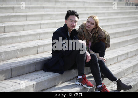 A couple of friends are sitting on the steps - Stock Photo