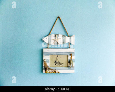 fish and picture frame hang on aqua light color wall - Stock Photo