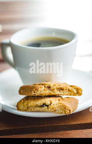 Sweet cookies and coffee cup on garden table. - Stock Photo