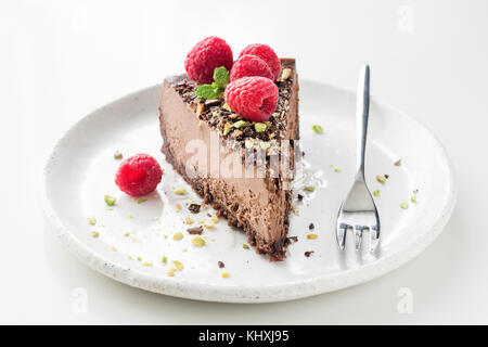 Slice of chocolate cake cheesecake decorated with crushed pistachio nuts, raspberries and mint leaf on white background. - Stock Photo