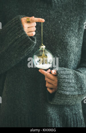 Woman in grey warm woolen sweater holding decorative glass ball - Stock Photo