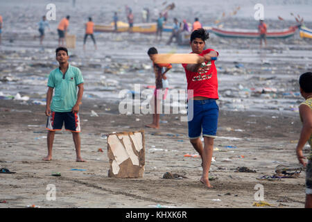 Indian teenage boys playing game of cricket among plastic garbage and other rubbish on Versova Beach, Mumbai