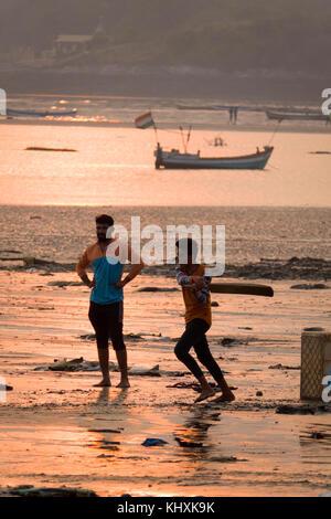 Young men playing cricket at sunset on Versova Beach, Mumbai