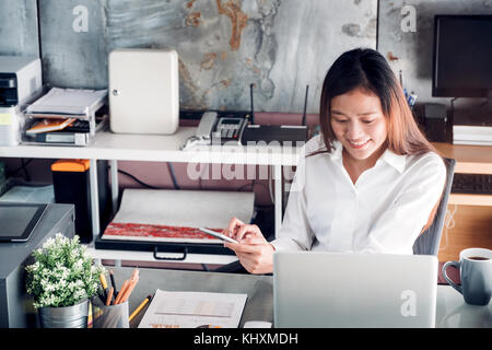 Asian businesswoman chattin on mobile phone in front of laptop computer at office,Office lifestyle concept. - Stock Photo