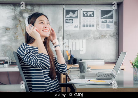 Young asian casual businesswoman arm on desk rest pose with laptop computer and listening music via headphone at - Stock Photo