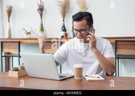 asia casual man arm up celebrate good new from mobile at laptop in coffee shop,success business concept,work outside - Stock Photo