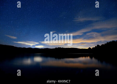 Night with stars in park over lake in Stowe, VT. - Stock Photo