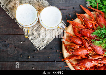 A  pile of tasty boiled crawfish on a round wooden tray and two mugs of cold beer on a dark background. Top view. - Stock Photo