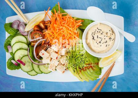 Rectangular rainbow vegan plate with vegetables, tofu and hummus. Vegetarian detox food concept. Blue background, - Stock Photo