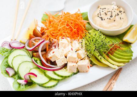 Vegan lunch salad with tofu, hummus and vegetables. Vegetarian detox food concept. - Stock Photo