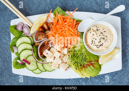 Vegan rainbow bowl with vegetables, hummus and tofu. Dark background, top view, vegan detox food concept. - Stock Photo