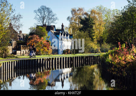 Couple pushing a pushchair walking on canal towpath in Vines Park in autumn. Droitwich Spa, Worcestershire, England, - Stock Photo