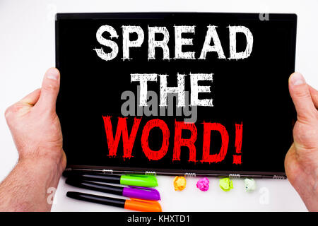 Spread The Word text written on tablet, computer in the office with marker, pen, stationery. Business concept for - Stock Photo