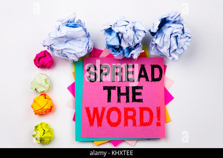 Writing text showing Spread The Word written on sticky note in office with screw paper balls. Business concept for - Stock Photo