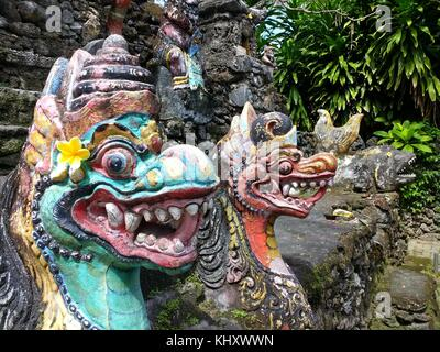 Close up of brightly painted dragon gods with offering of egg in mouth at sea temple near Sanur on Indonesian island - Stock Photo