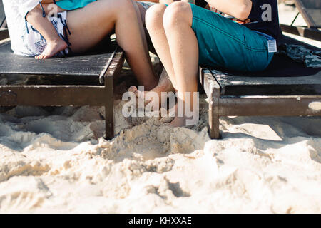 Mother and son sitting on sun loungers, mother holding young daughter, low section - Stock Photo