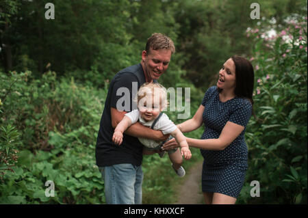Pregnant couple swinging toddler son on pathway - Stock Photo
