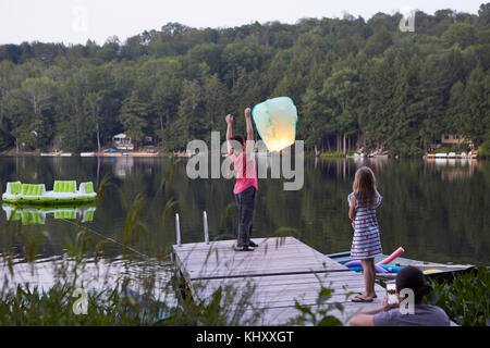 Girl standing on jetty releasing sky lantern, young girl watching, woman photographing event using smartphone - Stock Photo