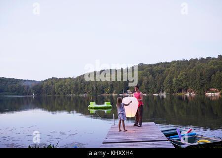 Two girls standing on jetty, releasing sky lantern - Stock Photo