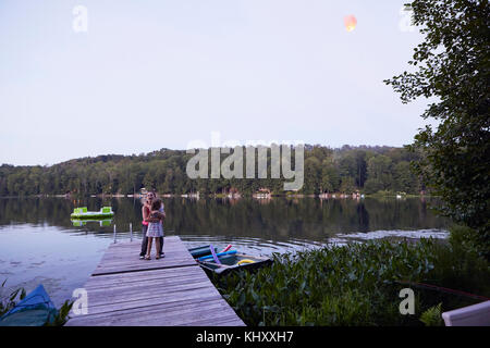 Two girls standing on jetty, hugging - Stock Photo