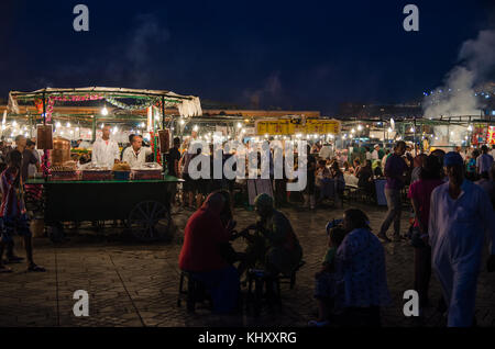Marrakesh, Morocco - September 05 2013: Food stands with smoke and light on famous Jamaa el Fna square in evening - Stock Photo