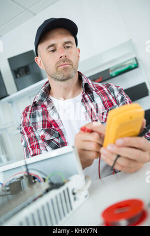 Electrician using multimeter - Stock Photo