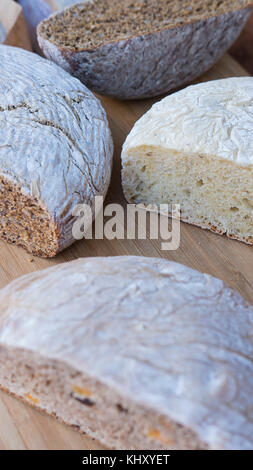 Vertical shot of different types of healthy, organic breads: brown, white, with nuts and seeds, cut in half, displayed - Stock Photo