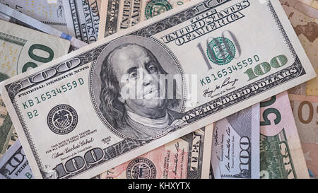 Pile of different denominations dollar banknotes with focus on one hundred dollar bill on top - Stock Photo
