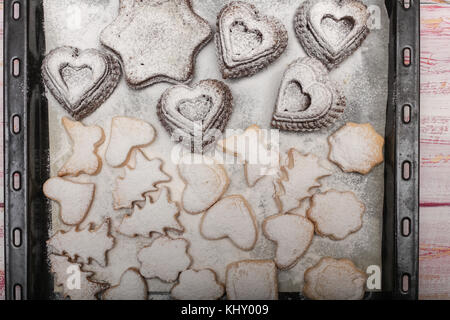 Freshly baked traditional new year cookies on tray on wooden background from above - Stock Photo