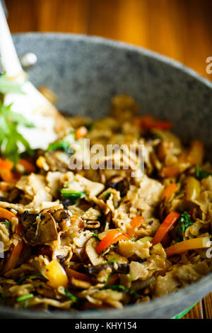 Buckwheat homemade noodles with fried mushrooms and vegetables - Stock Photo