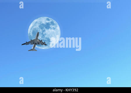 Jumbo jet aeroplane crossing daytime moon - Stock Photo