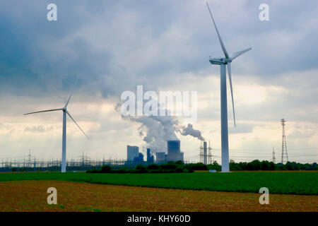 Power generation with old and new technology: Wndmills in the foreground, brown coal power plant in the background. - Stock Photo
