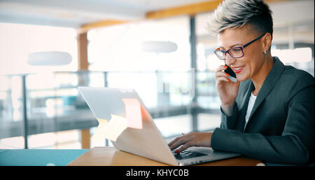 Attractive young female architect working on laptop - Stock Photo