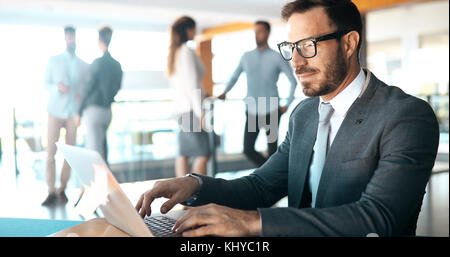 Professional businessman working on laptop in office - Stock Photo