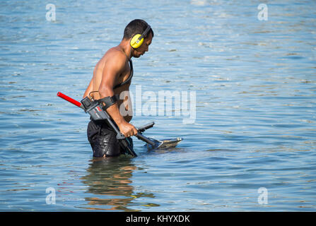 Man metal detecting with metal detector in the sea. - Stock Photo