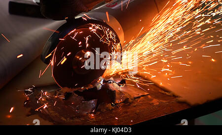 Cutting metal with disc grinder with bright sparks - Stock Photo