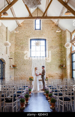 Couple Standing At Church Altar During Wedding Ceremony