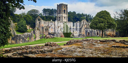 England, NorthYorkshire; the ruins of the 12th century Cistercian Abbey known as Fountains Abbey, one of the finest examples of monastic architecture in the world. The tower by Abbot Huby, (1495-1526), still dominates the valley landscape. Together with its surrounding 800 acres of 18th century landscaped parkland, Fountains Abbey has been designated a UNESCO World Heritage Site. North Yorkshire, England, UK. Ca. 1995.   Location: near Ripon, Yorkshire, England, UK.