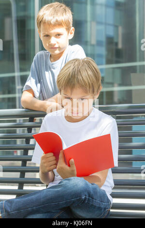 Schoolboys reading books. Kids doing homework outdoors. Back to school concept. - Stock Photo
