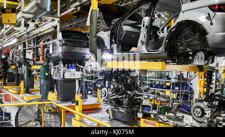 Workers on engine production line in car factory - Stock Photo