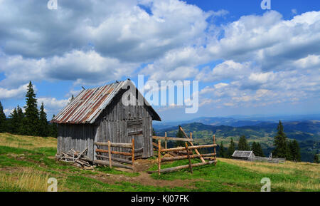 Small cabin located on the top of the hill with the view of the mountains and forest. - Stock Photo