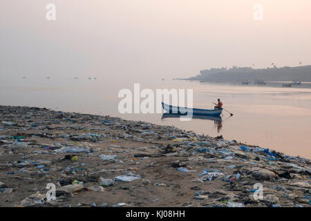 Fisherman paddles his boat past piles of plastic garbage and other rubbish on Versova Beach, Mumbai - Stock Photo