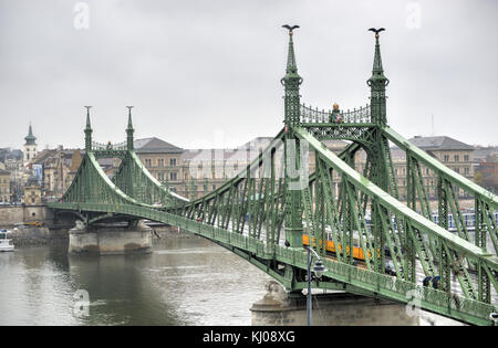 Liberty Bridge in Budapest, Hungary with a yellow tram crossing on a cloudy winter day. - Stock Photo