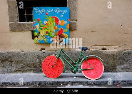 bicycle leaning against wall with melon effect wheels, florence, italy - Stock Photo