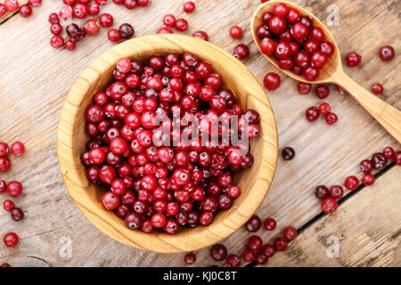 ripe cranberries on a wooden background, organic vitamin product for strengthening immunity - Stock Photo