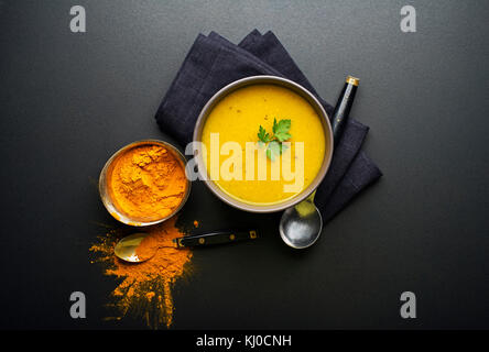 Healthy turmeric or curcuma cream soup on black background - Stock Photo